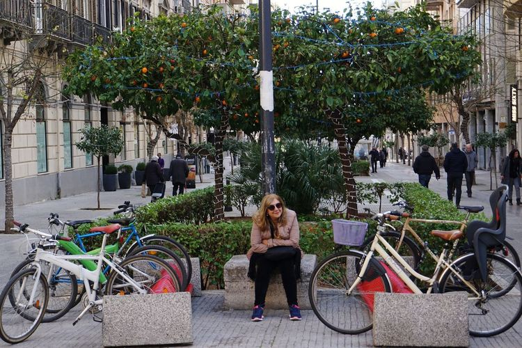 Full length of woman wearing warm clothing sitting by bicycles in city