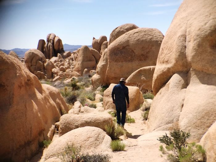 Rear view of man walking amidst rock formation on sunny day