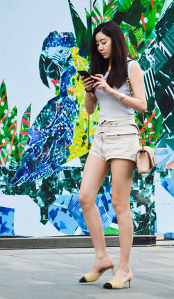 Beautiful Woman Casual Clothing Communication Day Fashion Front View Full Length Happiness High Heels Holding Leisure Activity Lifestyles Long Hair Mobile Phone One Person Portable Information Device Posing Real People Smiling Standing Technology Using Phone Wireless Technology Young Adult Young Women