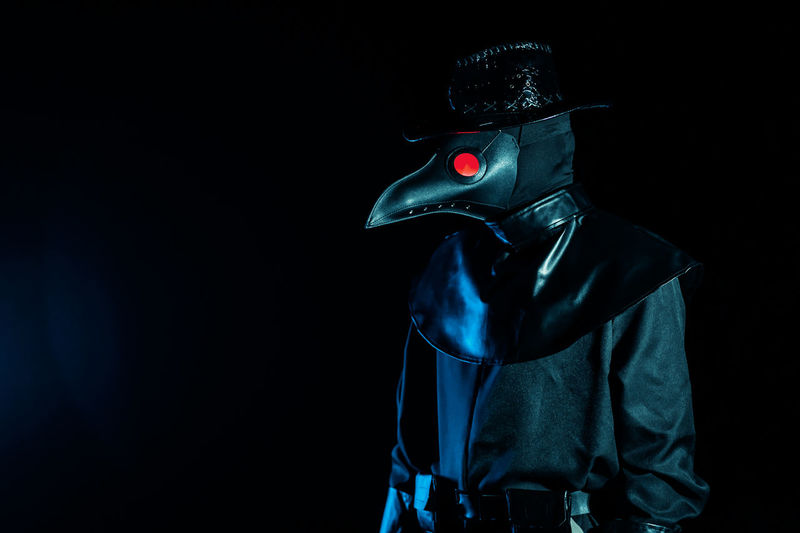 Midsection of person wearing mask against black background