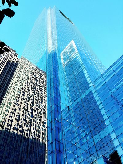 Low angle view of modern skyscrapers against blue sky