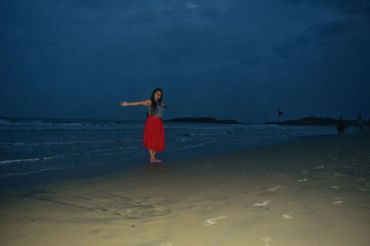Woman with arms outstretched standing at beach against sky