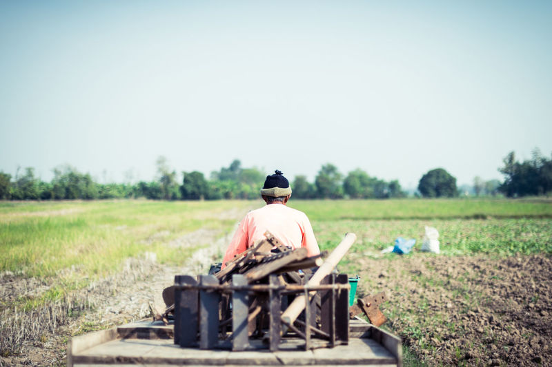 Rear View Of Man Carrying Scrap Metal On Cart Through Field Against Clear Sky