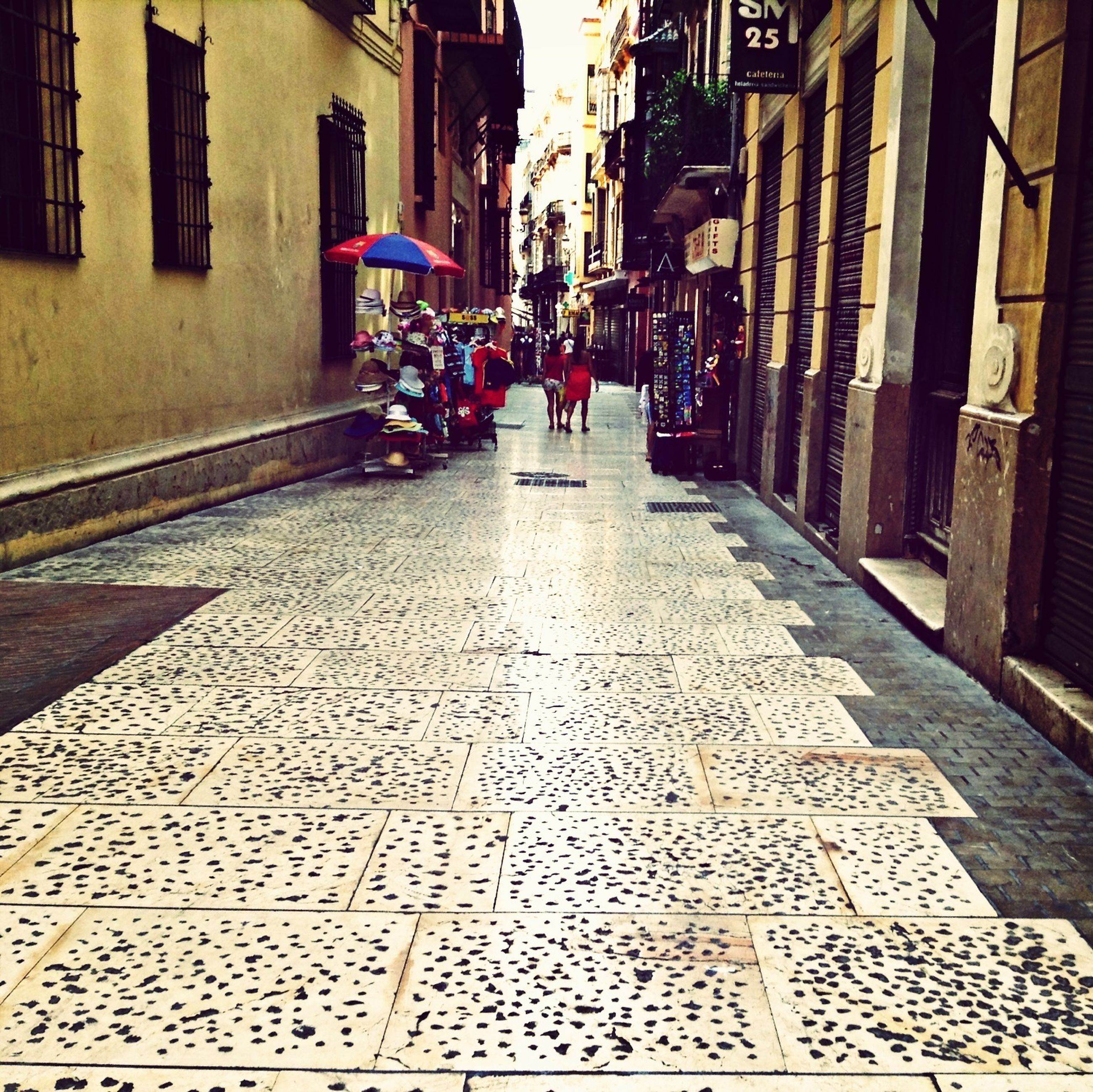 building exterior, architecture, built structure, street, city, the way forward, building, residential building, city life, alley, residential structure, cobblestone, diminishing perspective, city street, incidental people, transportation, large group of people, day, walking