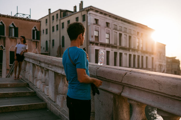 Venice Architecture Built Structure Building Exterior City Men Real People Lifestyles Leisure Activity Three Quarter Length Building Standing One Person Casual Clothing Railing Young Adult Young Men Nature City Life Day Outdoors Lens Flare