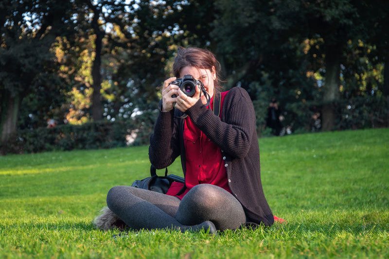 Young woman photographing camera on grass