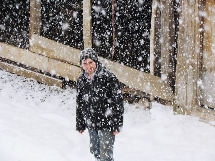 Portrait Of Man Standing On Field During Snowfall