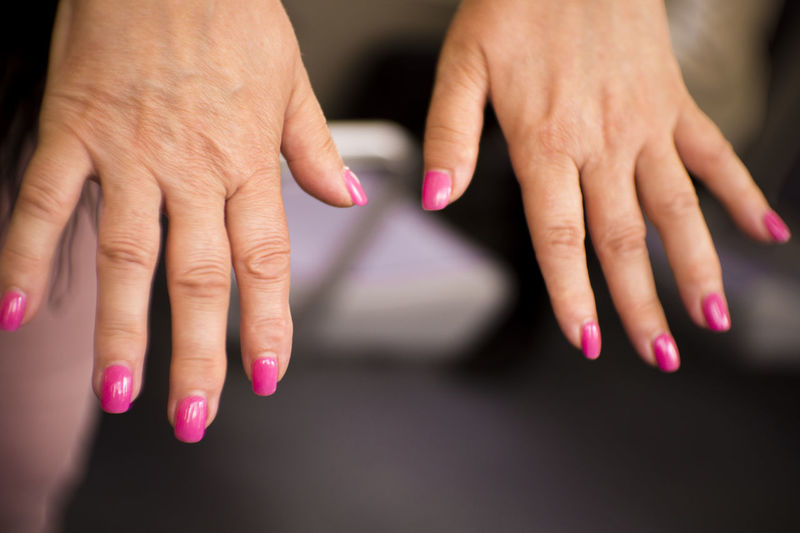 Close-up of woman hand with pink nail polish