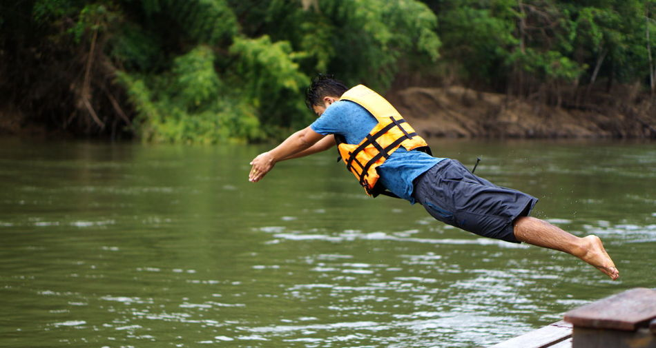 Side view of man diving in lake