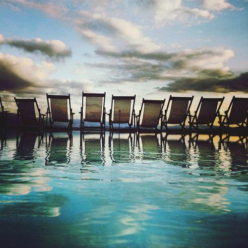 Row of deck chairs by infinity pool