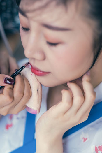 A young woman in Chinese Han clothing. Real People One Person Applying Lifestyles Make-up Women Leisure Activity Headshot Human Body Part Close-up Indoors  Holding Human Hand Body Part Females Focus On Foreground Adult Portrait Young Adult Hand Human Face Beautiful Woman Human Lips Han Clothing Chinese Food Traditional Dress Wear Style Makeup