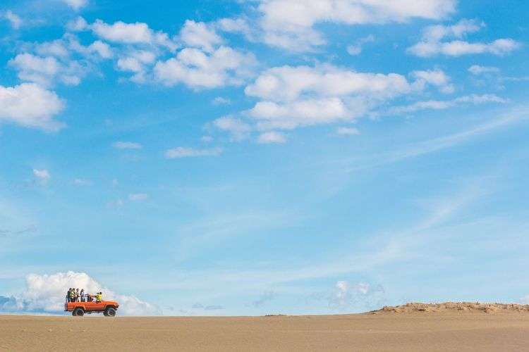 People on off-road vehicle in desert against cloudy blue sky during sunny day