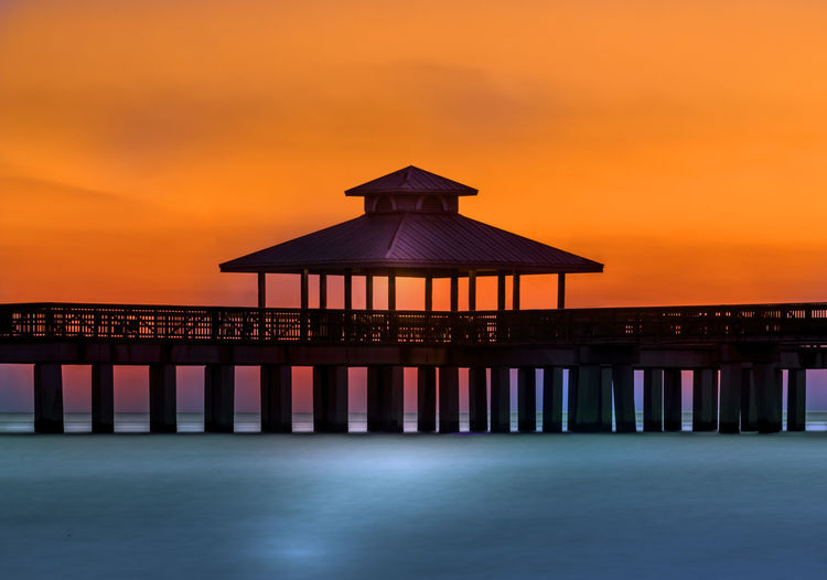 Built structure on pier over sea against orange sky during sunset