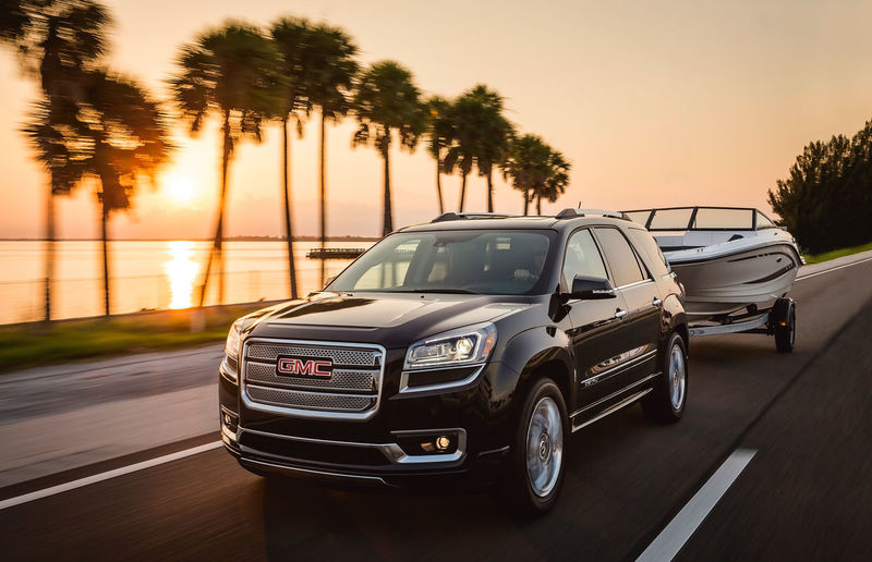 Black GMC SUV towing a boat past palm trees on a highway in Florida Automobile GMC SUV Towing Transportation Boat Car Highway Land Vehicle Luxury Mode Of Transportation Motor Vehicle Orange Color Outdoors Plam Trees Reflection Road Trip Sky Sunlight Sunrise Trailer Transportation Travel Tree Vehicle Interior