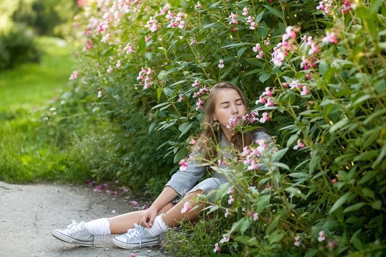 Cute girl smelling flower outdoors