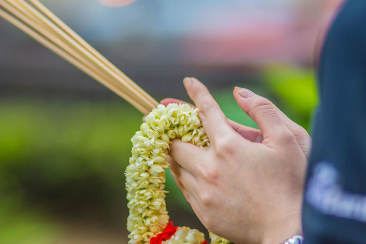 Cropped Hands Of Woman Holding Incense Sticks With Floral Garland In Temple