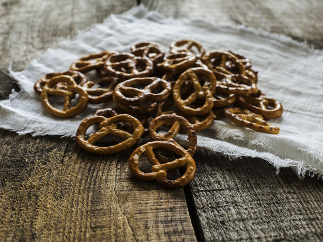 Heap of fresh Wheat salt pretzels on hessian linen fabric cloth and wooden table Close-up Cloth Fabric Focus On Foreground Fresh Group Of Objects Heap Hessian Intricacy Linen Pearl Pretzels Salt Surface Level Table Wheat Wooden