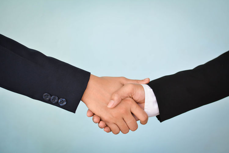 Cropped image of business people giving handshake against blue background