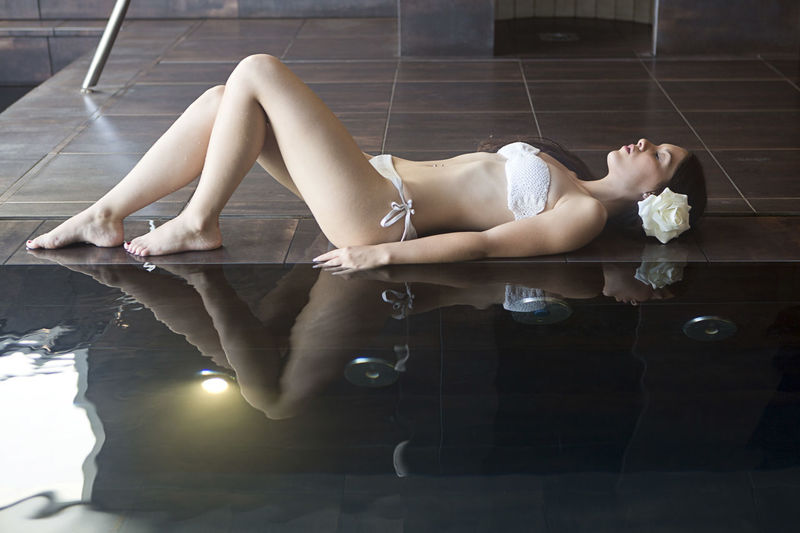 Full length young woman in bikini sleeping by swimming pool