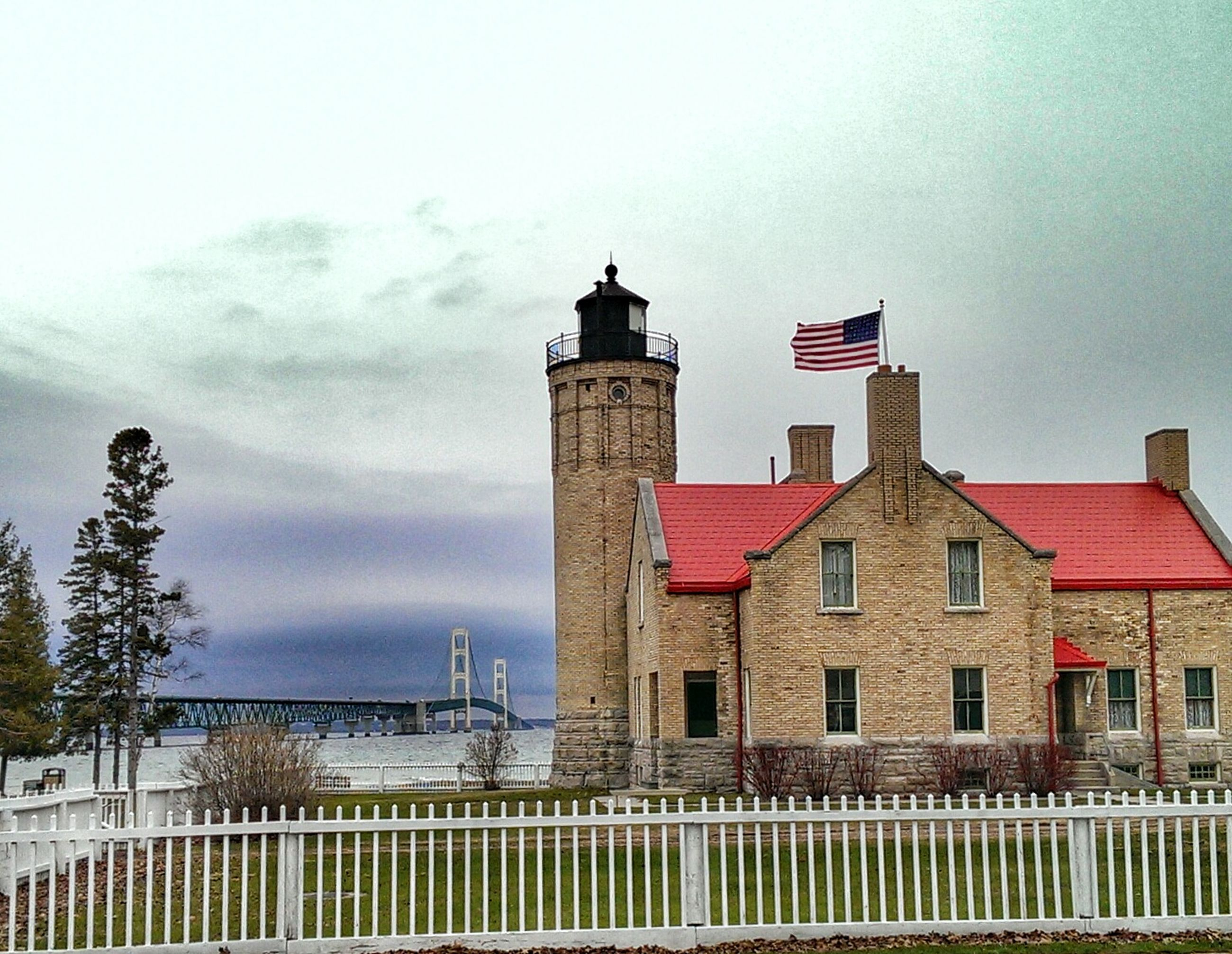 architecture, building exterior, built structure, sky, low angle view, lighthouse, tower, protection, cloud - sky, day, guidance, building, red, outdoors, safety, city, no people, security, window, flag