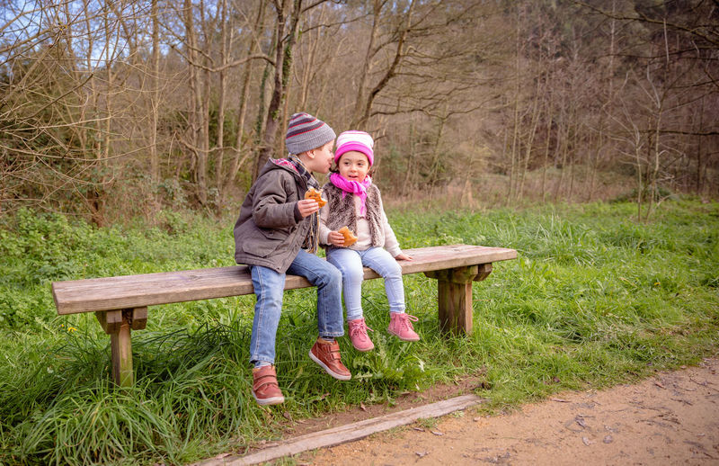 Full length of cute siblings having food while sitting on bench in park