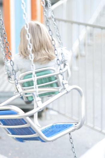 Girl sitting in chain swing ride