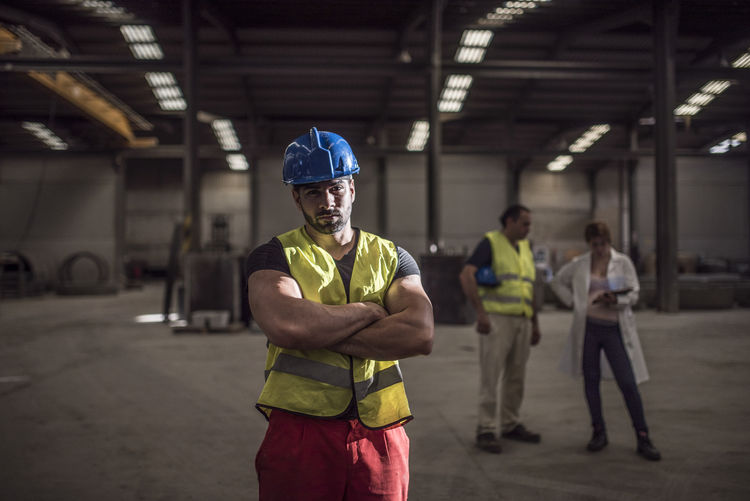 Young man standing with colleagues working in background at factory