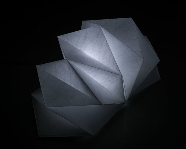 """My study of the incredible Hoshigame light by Issey Miyake, as exhibited in the Manchester Art Gallery. Made from recycled plastic, this is to me a prime example of exceptional design and is a real inspiration. As quoted from the Artemide website """"the IN-EI ISSEY MIYAKE lighting collection [of which the Hoshigame is just one example] is a collection of free-standing, table and hanging lights. Each lampshade is created using 2 or 3D mathematic principals, where light and shade harmoniously alternate. Miyake's unique folding technology creates both statuesque forms as well as sufficient solidity. The structure of the recycled material, together with an additional surface treatment allows these shades to perfectly keep their shape without the need for internal frame, and to be re-shaped when needed. They can be easily stored flat when not in use"""". GENIUS!! 3D Abstract Artemide Black Background Close-up Cool Design In-Ei Issey Miyake Issey Miyake Japan JAPANESE Design Light Lighting Manchester Art Gallery Modern No People Shape Your Design Story"""
