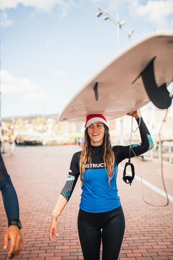 Smiling young woman carrying surfboard on head in city