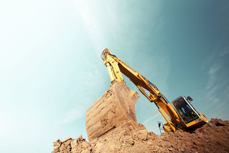 Construction site Excavator Working Hard Workplace Bulldozer Construction Equipment Construction Industry Construction Machinery Construction Site Day Deserted Dirt Earth Mover Equipment Excavator Shovel Industrial Equipment Industry Large Machinery Metal No People Outdoors Rock Sky Solid Sunlight