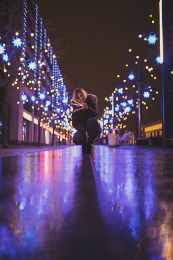 Surface level of woman crouching on footpath against sky at night