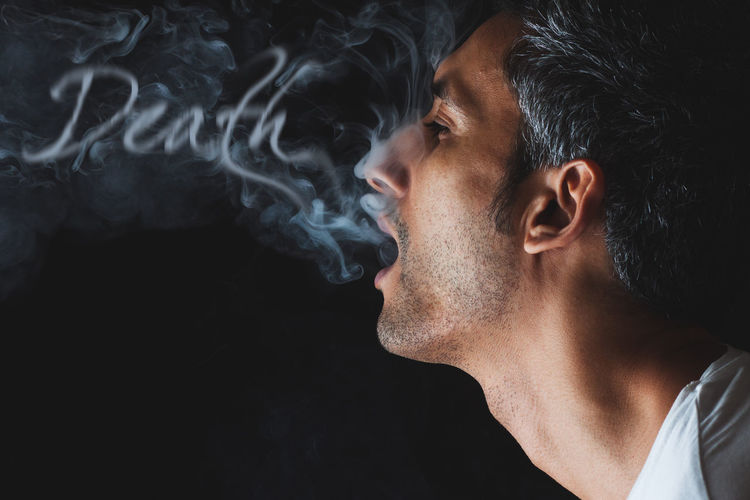 Close-Up Of Man Exhaling Smoke Against Black Background