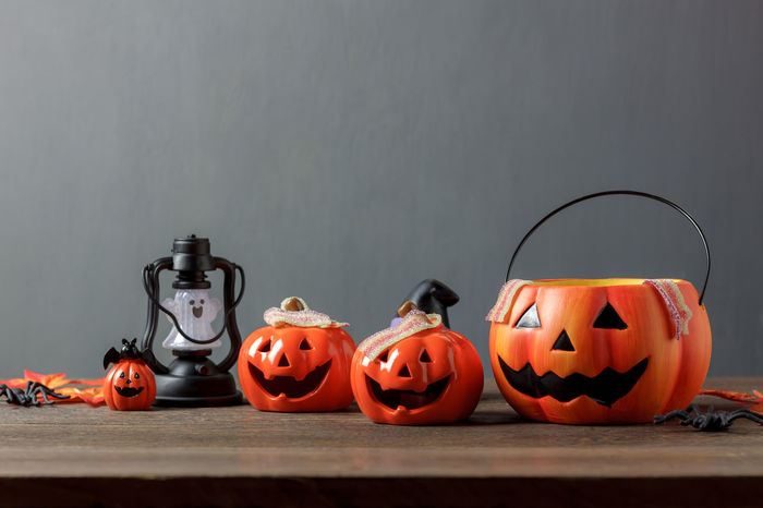 Mix difference objects of Happy Halloween decoration festival concept background.Essential accessory items on modern rustic brown wooden at home office studio desk.Grunge grey wallpaper and copy space Anthropomorphic Face Candy Celebration Cultures Day Food And Drink Halloween Holiday - Event Indoors  Jack O Lantern Jack O' Lantern Lantern No People Pumpkin Table Tradition