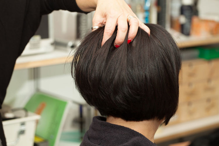 Midsection of hairdresser with hand in woman hair at salon