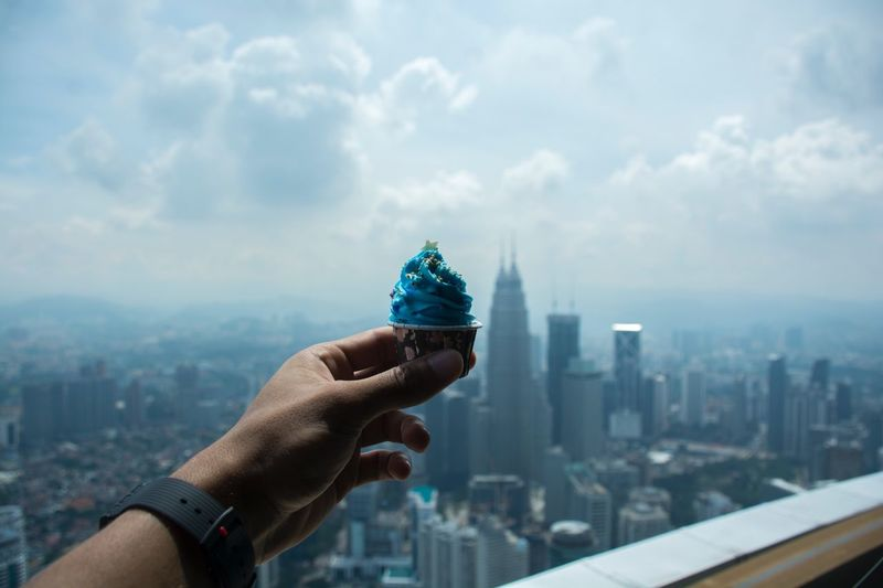 Close-up of man holding cupcake  against cityscape