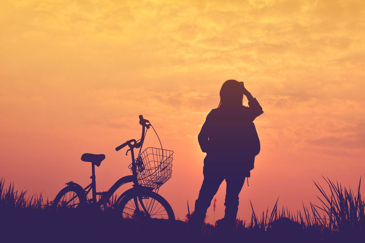 Silhouette person with bicycle against sky during sunset
