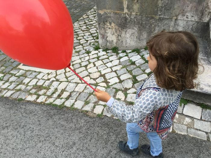 High angle view of girl with balloon standing outdoors