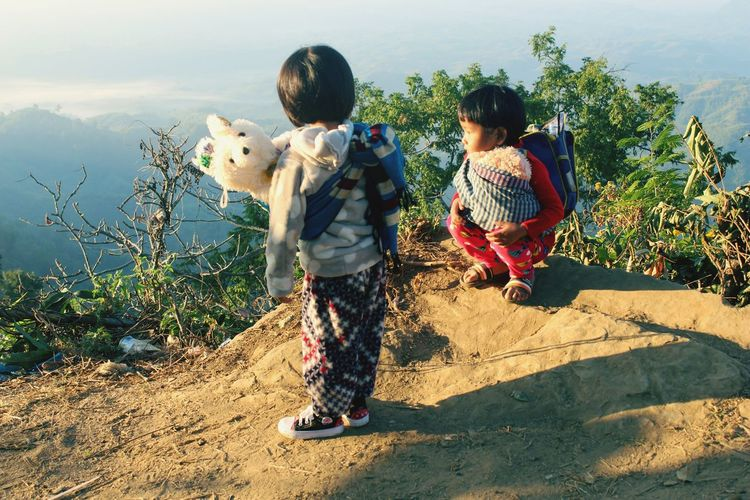 Sisters with toys on cliff