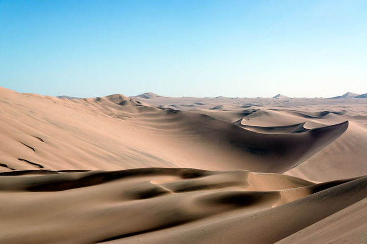 Scenic View Of Desert Against Clear Blue Sky At Huacachina
