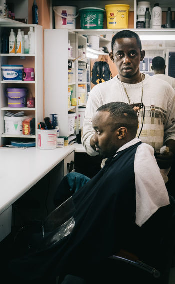The Barber Africa Barber Body Care Business Finance And Industry Capetown Customer  Haircut Human Representation Indoors  Lifestyle Men Occupation Only Men People Person Shaved Head Skill  Small Business Streetphotography Working Young Men The Street Photographer - 2017 EyeEm Awards