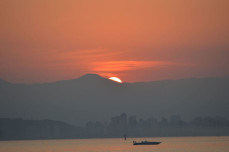 Scenic View Of Sea And Silhouette Mountains Against Orange Sky