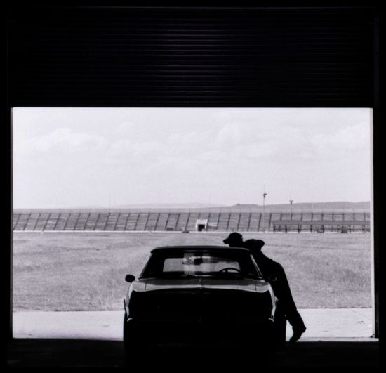 Silhouette Man Cleaning Car At Field Against Sky