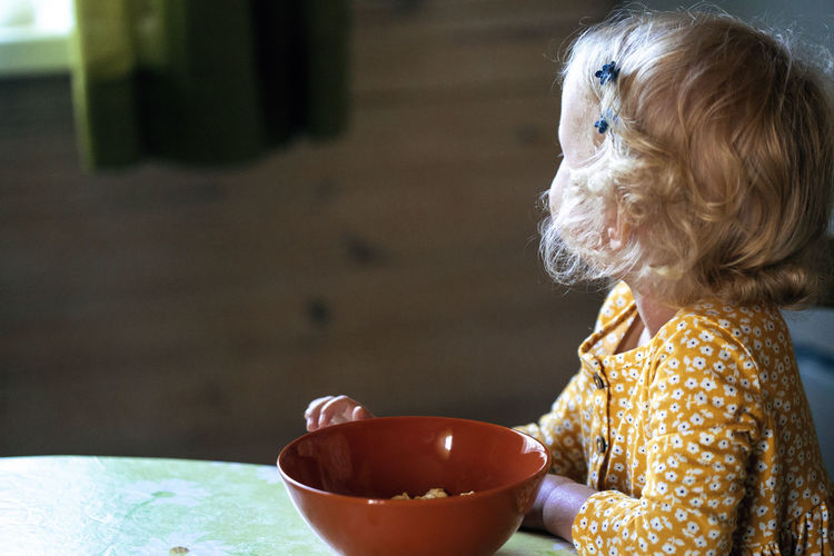 Close-up of girl with bowl on table at home