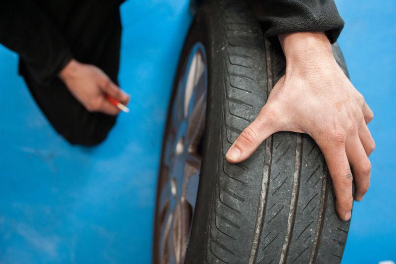 Cropped image of mechanic repairing tire