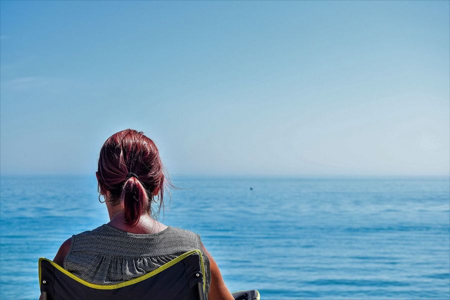 Beauty In Nature Clear Sky Day Horizon Over Water Lifestyles Looking Out To Sea Nature One Person Outdoors Real People Rear View Rear View Of Woman Looking Out To Sea Sea Sky Space For Copy Water Woman Sitting On The Beach Women