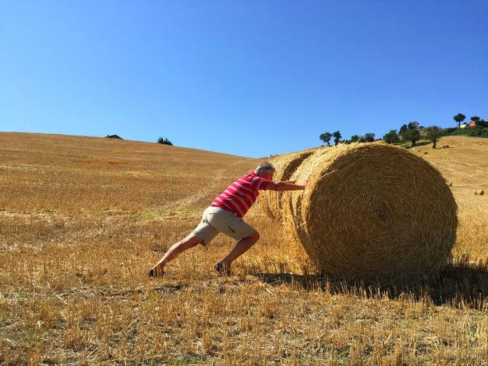 Full Length Side View Of Man Pushing Hay Bale On Field At Farm Against Blue Sky
