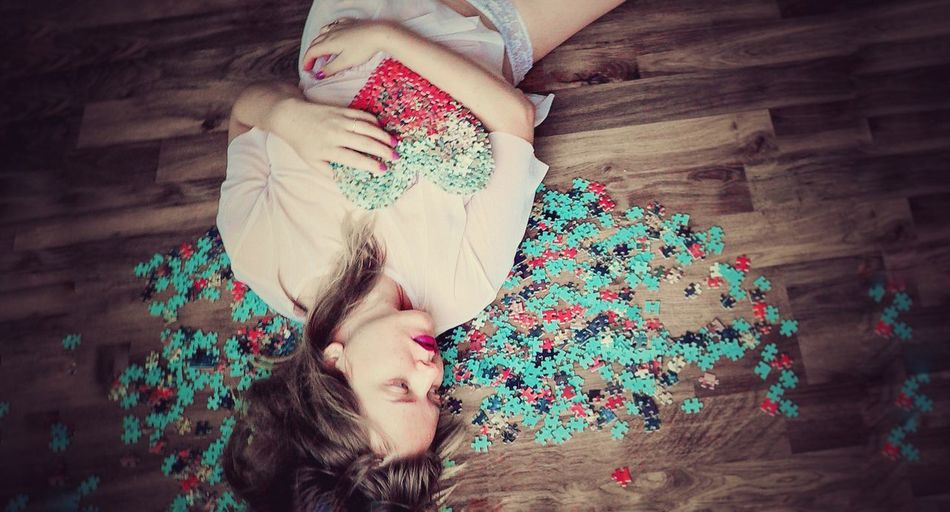 High Angle View Of Woman Lying Down Amidst Jigsaw Pieces On Hardwood Floor