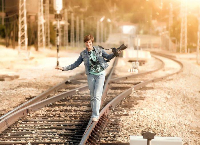 Photographer balancing on railroad tracks