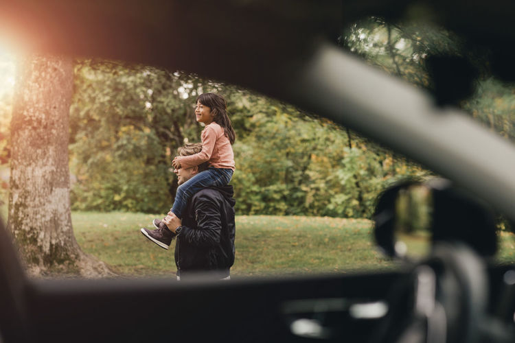 Rear view of man photographing woman sitting in car