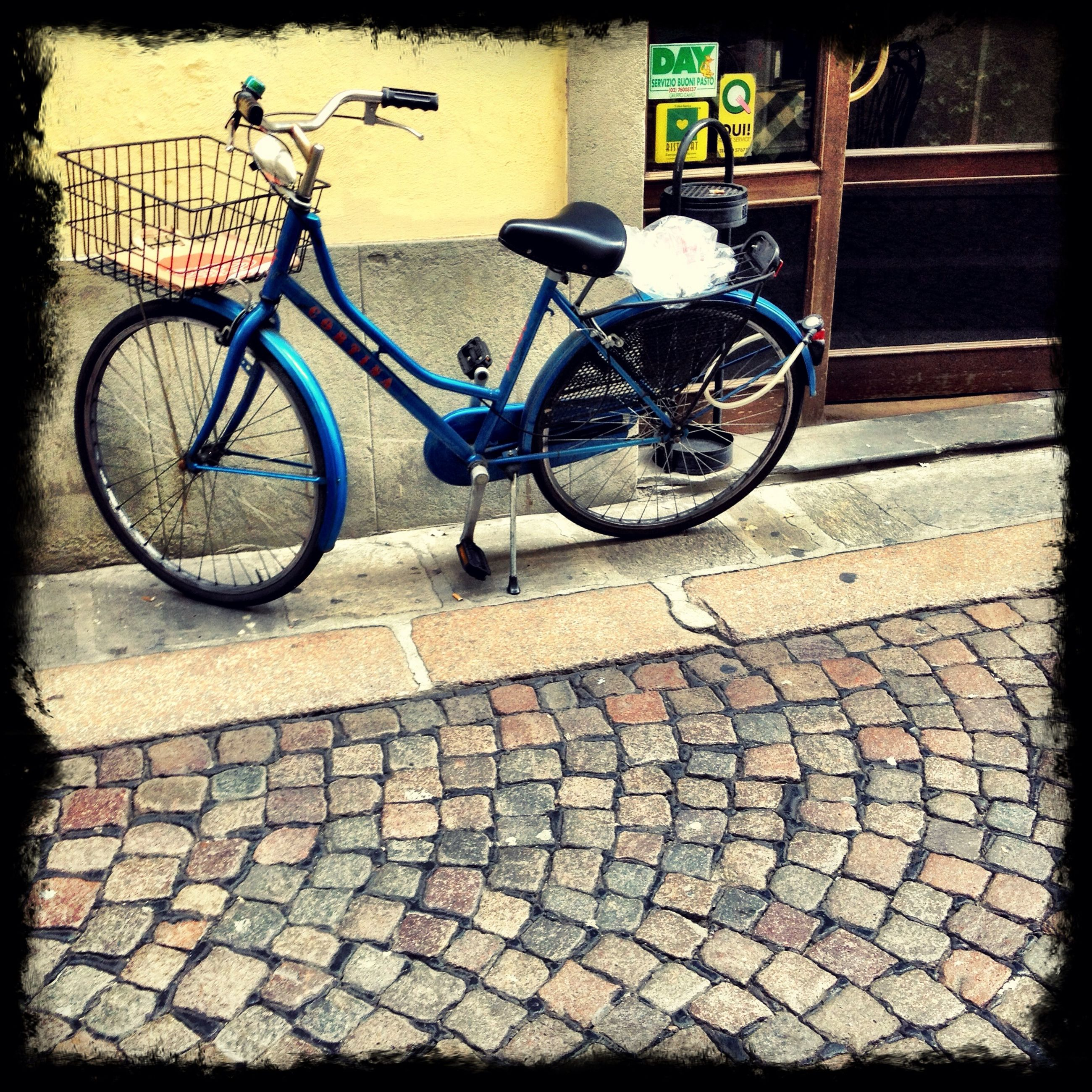 bicycle, transportation, mode of transport, land vehicle, stationary, parked, parking, street, wheel, transfer print, sidewalk, auto post production filter, cobblestone, outdoors, day, no people, sunlight, cycle, shadow, road